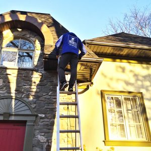 NICK'S Window Cleaning technician cleaning eavestrough