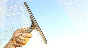man cleaning brampton area home window with squeegee