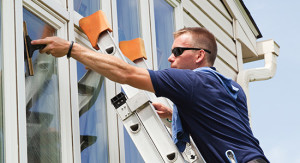 Technician from NICK'S Window Cleaning hard at work, cleaning the windows of a Greater Toronto home