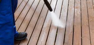 a worker is visible cleaning a deck using a power washer