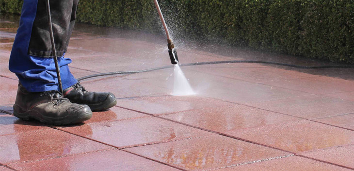 a worker is visible cleaning a patio using a high pressure washing system often refered to as power washing
