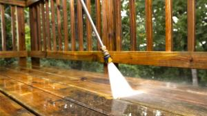 view of a pressure washer cleaning off a dirty deck, the contrast between the clean and dirty deck is clearly visible