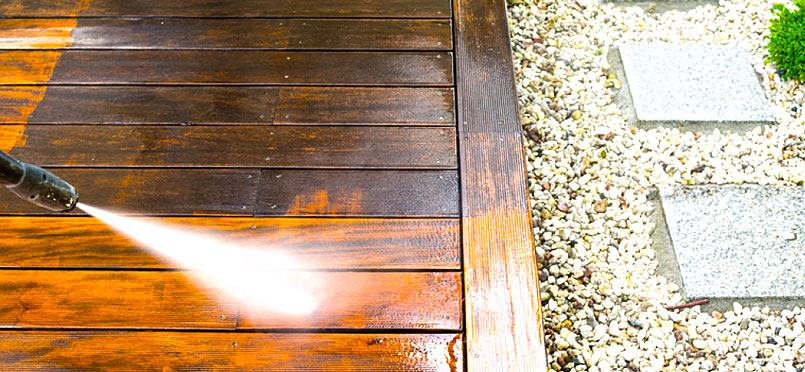 a worker power washing a deck with clear contrast of the dirty wood and clean wood, nearby a patio walkway is visible