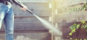 man power washing the interior of a fence located in the backyard of a toronto home