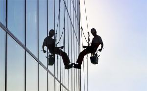 window cleaner sitting in bosun chair cleaning a high-rise office building
