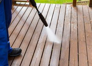 brampton power washing service being carried out by worker, a deck is visible in the process of being cleaned
