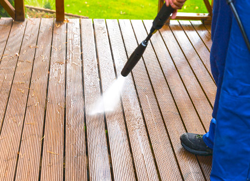 a worker provides etobicoke power washing services, cleaning a composite deck behind a beautiful home