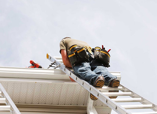 richmond hill eavestrough repair worker on a ladder inspecting and repairing gutters