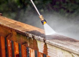 richmond hill power washing service being performed on a patio, the pressure washing wand is visible cleaning the railing of the deck
