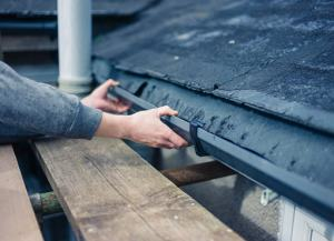 Thornhill eavestrough repair work being inspected by worker after completion