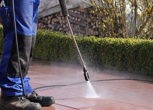 a worker provides Thornhill power washing service, cleaning a driveway