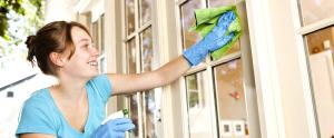 woman cleaning her home exterior, she is visibly cleaning a window and smiling