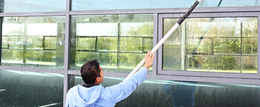 commercial window cleaner working on cleaning windows with a waterfed pole system