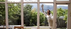 woman cleaning the exterior of her windows while standing on a patio