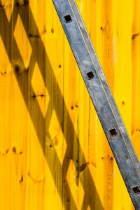 a ladder is seen leaning against a wall with a backdrop of yellow wood